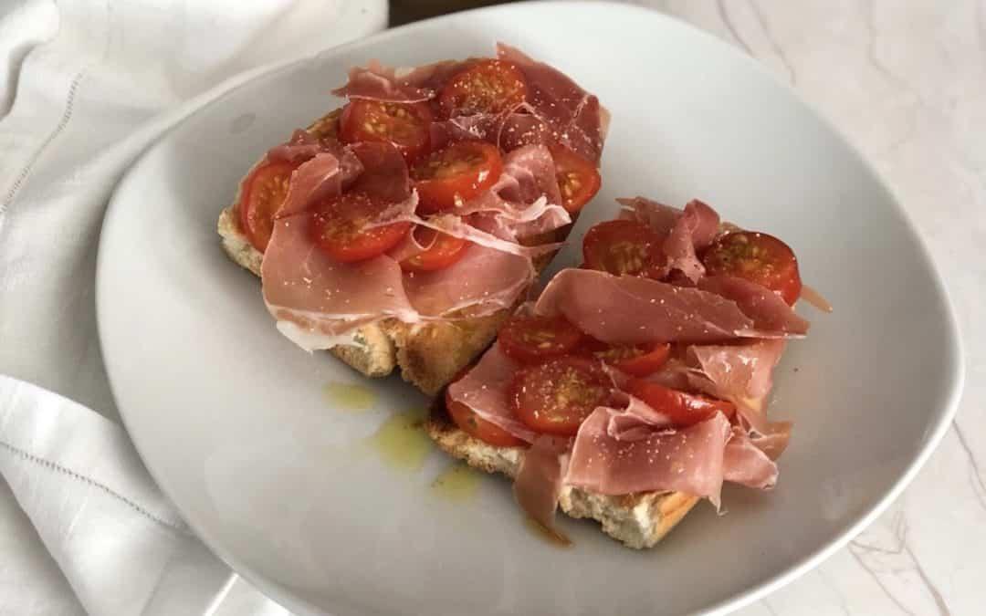 Tostadas de jamón con tomates cherrys y aceite de oliva.