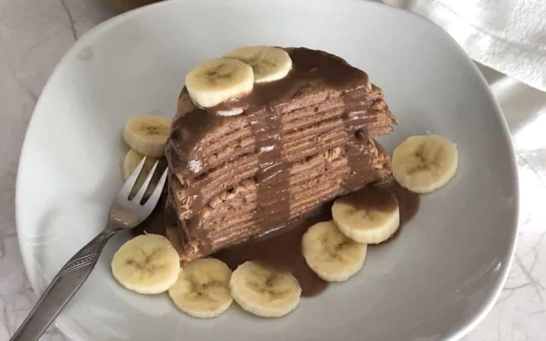 Torre de tortitas de avena con platano y chocolate con crema de cacahuete.