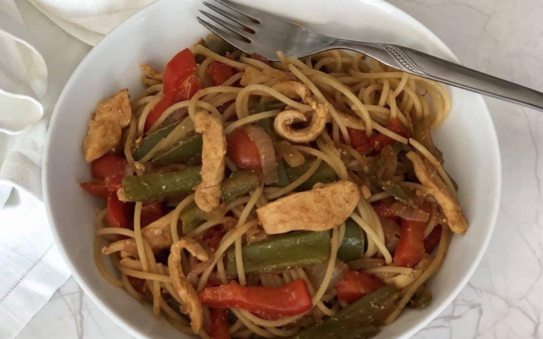 Espaguetis integrales salteados con pollo y verduras.